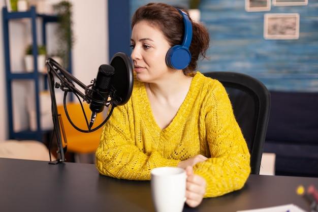 Influencerka w słuchawkach nagrywa nową serię podcastów dla publiczności. internetowa audycja internetowa na antenie, na której odbywa się transmisja strumieniowa treści na żywo w cyfrowych mediach społecznościowych, odbywa się za pomocą sieci internetowej.