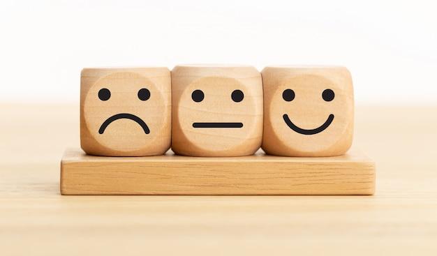 Informacje zwrotne na temat obsługi użytkownika, ocena i ocena klienta, doświadczenie, koncepcja badania satysfakcji. drewniane klocki z wyrazem twarzy