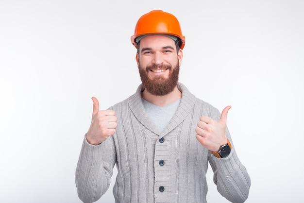 Ingineer, architekt lub konstruktor w twardym kapeluszu pokazującym gest, obie kciuki do góry.