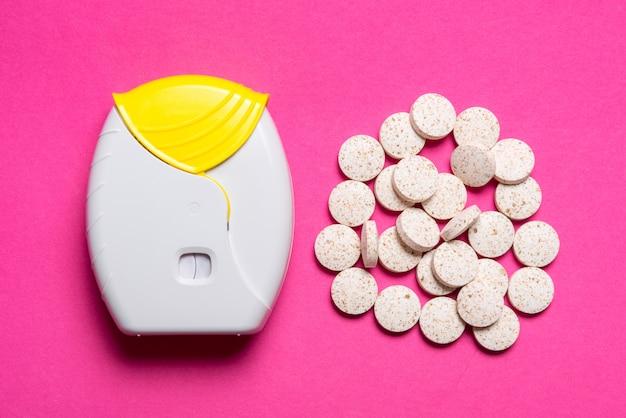 Inhalator i tabletki na różowym tle