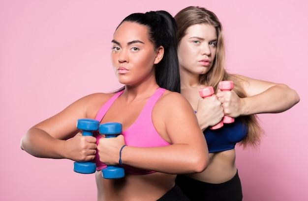 Inne podejście. dwie młode atrakcyjne kobiety z nadwagą trzymając drobne hantle stojąc.