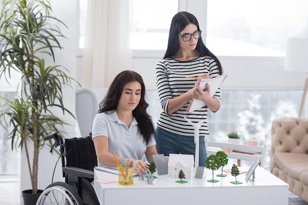 Innowacja ekologiczna. mądry kolega zostaje i kaleka kobieta pomaga przy modelu