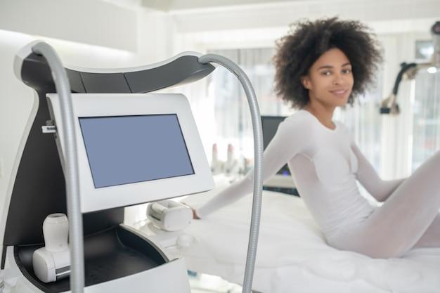 Innowacja w kosmetologii. zadowolona dziewczyna w specjalnym ubranku czeka na zabieg na kanapie w centrum kosmetologii