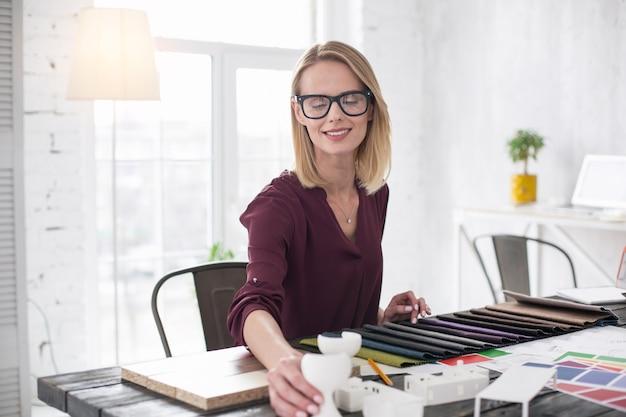 Innowacyjne elementy. zamyślona projektantka siedzi przy stole i wybiera tapicerkę