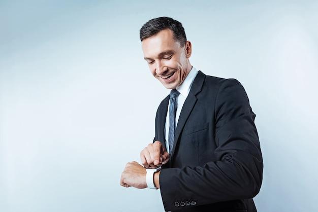 Innowacyjne technologie. niski kąt ujęcie pozytywnie nastawionego biznesmena dotykającego ekranu elektronicznego zegarka na nadgarstku z radosnym uśmiechem na twarzy.