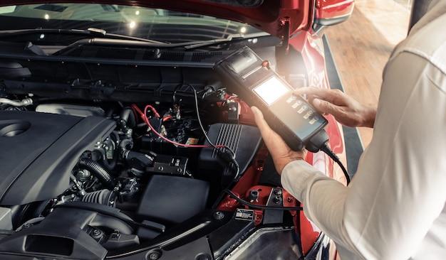 Inspekcja człowieka z woltomierzem tester pojemności akumulatora. do konserwacji serwisowej naprawy silnika do silnika. w fabrycznym transporcie obrazu motoryzacyjnego