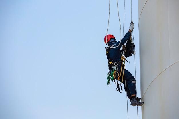 Inspekcja dostępu linowego męskiego pracownika w przemyśle zbiorników o grubości.