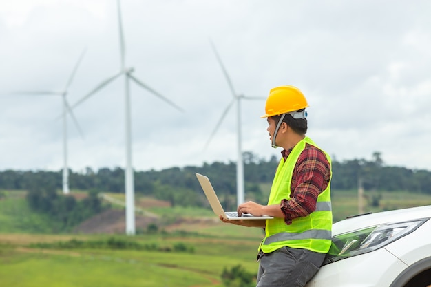 Inspekcja i weryfikacja inżyniera wiatraka turbina wiatrowa na placu budowy używając samochodu jako pojazdu.