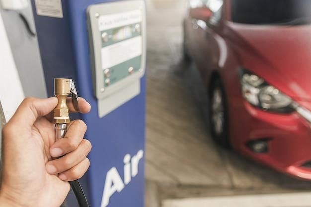 Inspekcja samochodu azjatyckiego człowieka zmierz ilość napompowane gumowe opony samochodowe. zbliżenie dłoni trzymającej maszynę napompowany manometr do pomiaru ciśnienia w oponach samochodowych dla motoryzacji, wizerunek samochodu