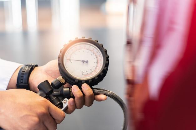 Inspekcja samochodu azjatyckiego człowieka zmierz ilość napompowane gumowe opony samochodowe. zbliżenie ręki trzymającej maszynę napompowany manometr do pomiaru ciśnienia w oponach samochodowych dla motoryzacji, wizerunek samochodu