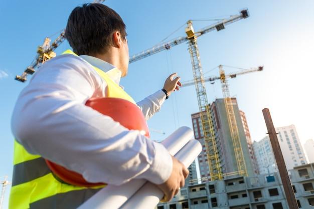 Inspektor budowlany patrzący w górę i wskazujący na budowany budynek