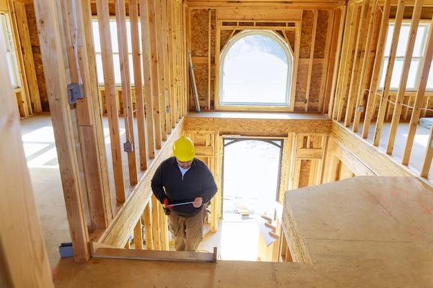 Inspektor budowlany patrzy na nowy dom trzymając tablet w kasku