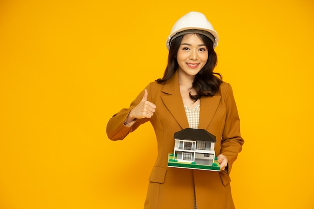 Inspektor domu azjatycka kobieta lub inżynier pokazujący kciuki do góry w białym kasku i trzymający model domu jednorodzinnego lub wolnostojącego domu na białym tle na żółtym tle