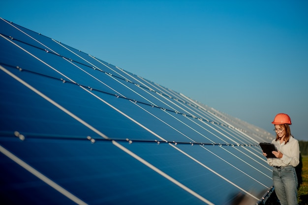 Inspektor inżynier kobieta trzymając cyfrowy tablet pracujący w farmie paneli słonecznych, park ogniw fotowoltaicznych, koncepcja zielonej energii.