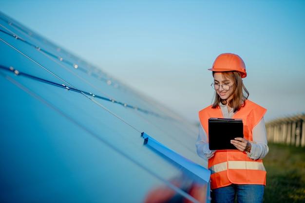 Inspektor inżynier kobieta trzymając cyfrowy tablet pracujący w farmie paneli słonecznych