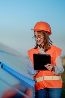 Inspektor inżynier kobieta trzymająca cyfrowy tablet pracujący w elektrowniach słonecznych