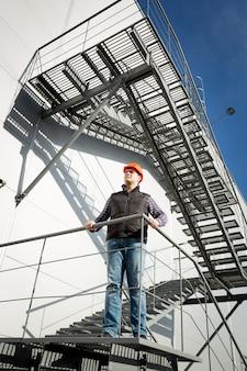 Inspektor nadzoru budowlanego stojący na metalowych schodach i patrzący na budynek