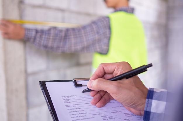 Inspektorzy sprawdzają projekt domu, w którym nieruchomość została przypisana do współpracy z inżynierem wykonawcy. jak również zanotuj szczegóły pracy, aby były gotowe i poprawne zgodnie ze wzorem.