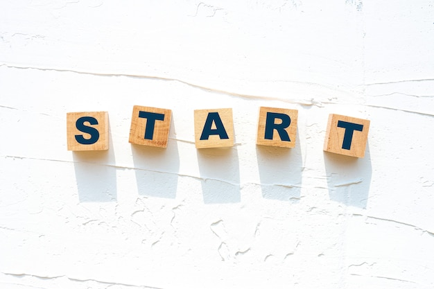 "Inspiracja cytuje tekst ""start"" na drewnianym bloku"