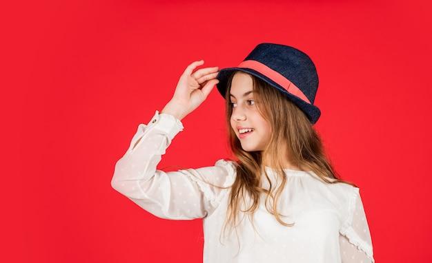 Inspiracja do stroju. indywidualny styl. dziewczyna nosić kapelusz czerwone tło. szczęśliwe dziecko w kapeluszu. modny dodatek. uczucie fantazji. letnia kolekcja akcesoriów. dziecko długie włosy nosić kapelusz. sklep z akcesoriami.