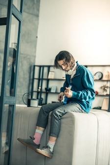 Inspiracja do zabawy. spokojny ciemnowłosy niezwykły mężczyzna ubrany w stylowy strój i relaksujący się na kanapie z gitarą