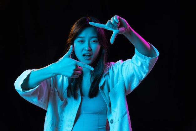 Inspiracja. portret azjatyckiej młodej kobiety na ciemnej ścianie w świetle neonu. piękna modelka ze słuchawkami. pojęcie ludzkich emocji, wyraz twarzy, młodość, sprzedaż, reklama.