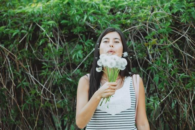 Inspirowana dziewczyna z bujnym bukietem mniszka lekarskiego w ogrodzie wśród zieleni latem. młoda dziewczyna z blowball kwitnie blisko zielonego żywopłotu w wiosna czasie. piękny portret kobiety
