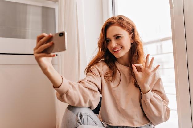 Inspirowana europejka w przytulnych ubraniach, dzięki czemu selfie. kryty portret uroczej rudej dziewczyny.