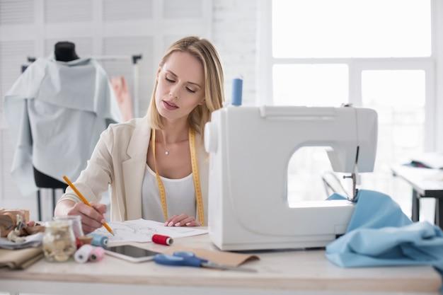 Inspirująca chwila. odblaskowa kobieta couturier za pomocą ołówka podczas szkicowania