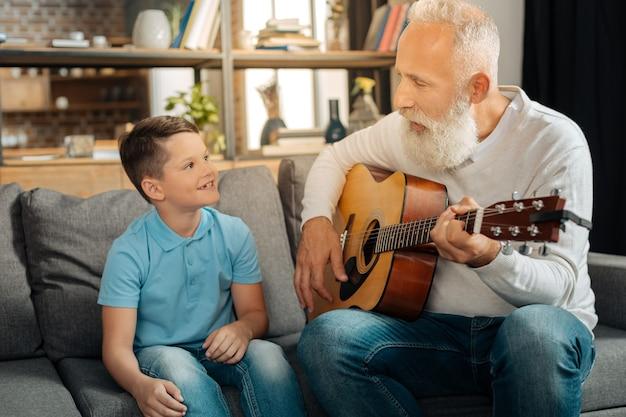 Inspirujące wibracje. przyjemny starszy pan siedzący na kanapie obok ukochanego wnuka i grający dla niego na gitarze, podczas gdy chłopiec patrzy na niego z podziwem