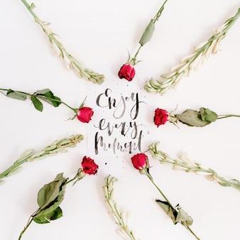 """Inspirujący cytat """"ciesz się każdą chwilą"""" napisany kaligrafią na papierze w ramce z czerwonych róż na białej powierzchni"""