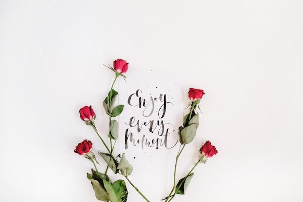 """Inspirujący cytat """"ciesz się każdą chwilą"""" napisany kaligrafią na papierze z czerwonymi różami na białej powierzchni"""