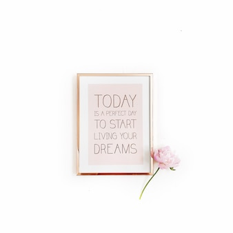 """Inspirujący cytat """"dziś jest idealny dzień, aby zacząć spełniać swoje marzenia"""". minimalna złota ramka na zdjęcia i różowy kwiat piwonii na białym tle"""