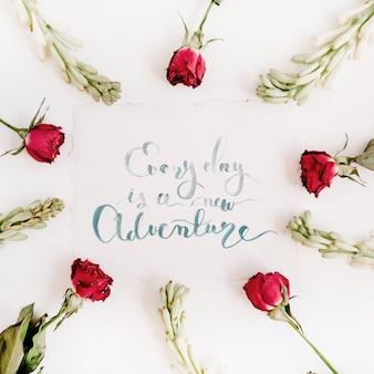 """Inspirujący cytat """"everyday is a new adventure"""" napisany kaligrafią na papierze w ramkę czerwonych róż na białej powierzchni"""
