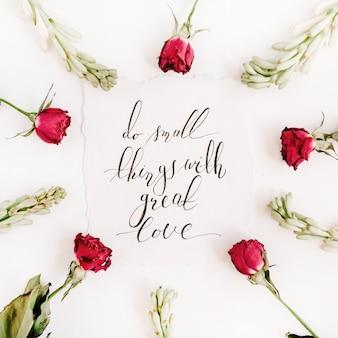 """Inspirujący cytat """"rób małe rzeczy z wielką miłością"""" napisany kaligrafią na papierze w ramkę czerwonych róż na białej powierzchni"""