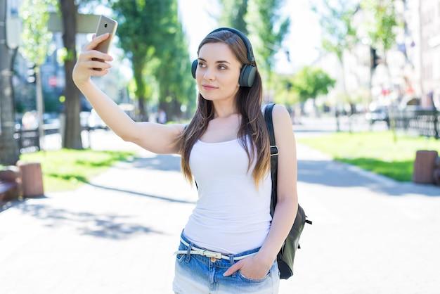 Instagram influencer gadżet urządzenie koncepcja odzieży dżinsowej studenta. portret całkiem atrakcyjnej, wspaniałej ładnej, pewnej siebie pani zrobić selfie w parku miejskim weekendowej podróży turystycznej
