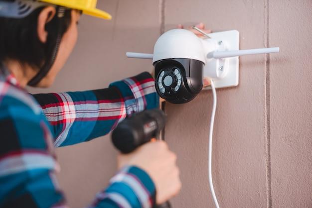 Instalacja cctv z udziałem młodych azjatyckich techników. instalacja taka jak kamera ip wi-fi: bezprzewodowa kamera ip
