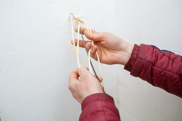 Instalacja elektryczna. podczas naprawy. otwórz przewody. wystające na białym tle na białej ścianie. profesjonalny montaż elektryczny