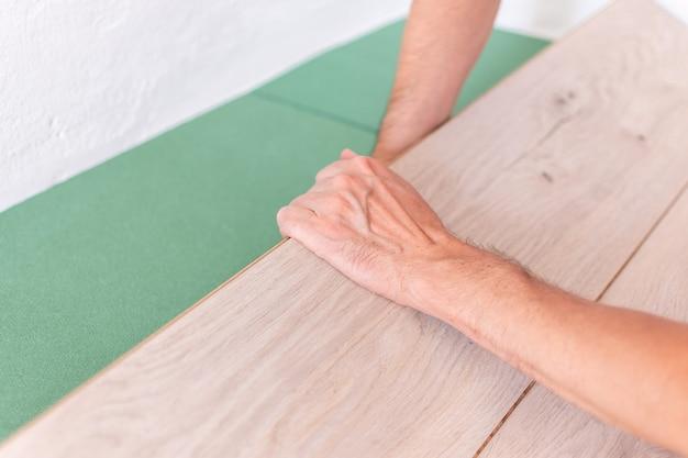 Instalacja laminatu lub parkietu w pomieszczeniu, pracownik montujący drewnianą podłogę laminowaną, przyjazne dla środowiska arkusze dźwiękochłonne