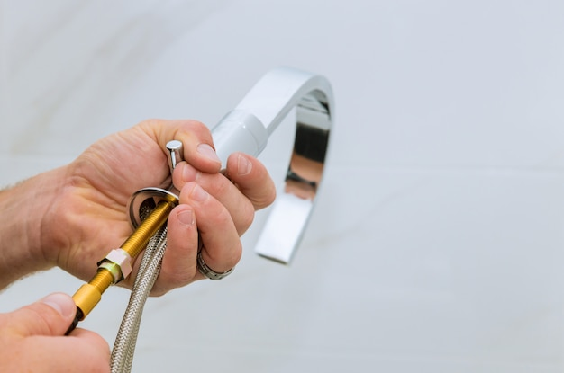 Instalowanie kranu wodnego w hydrauliku łazienkowym w pracy w łazience