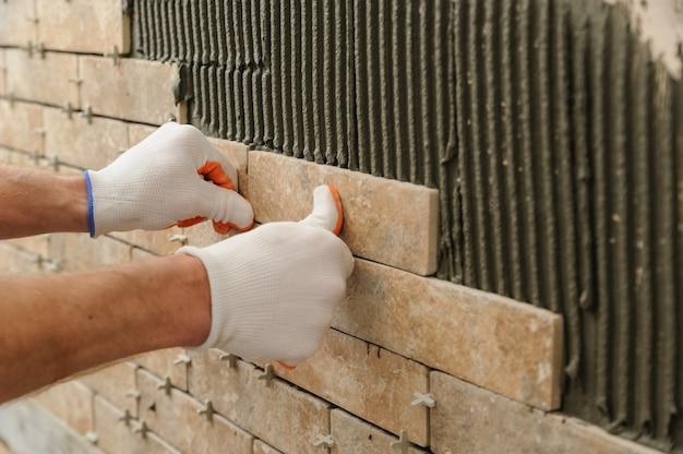 Instalowanie płytek na ścianie.