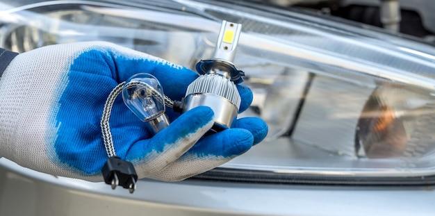 Instalowanie zamiennika nowej, nowoczesnej żarówki halogenowej led do samochodu. mechanik trzyma lampę samochodową