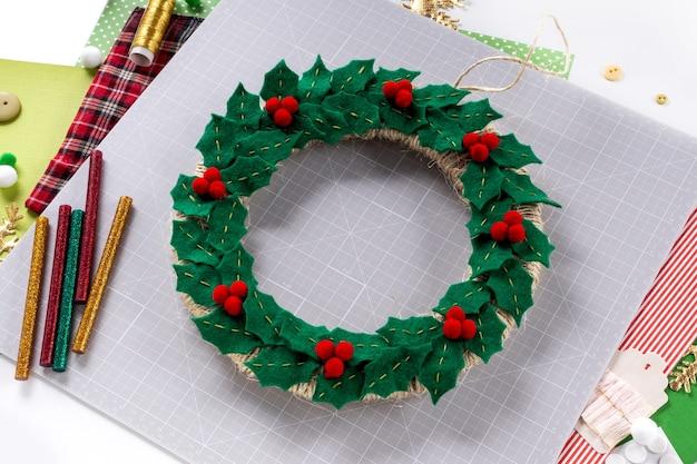 Instrukcja dla majsterkowiczów. wykonanie świątecznego wieńca z filcu. narzędzia i materiały rzemieślnicze. krok 7 - finał.