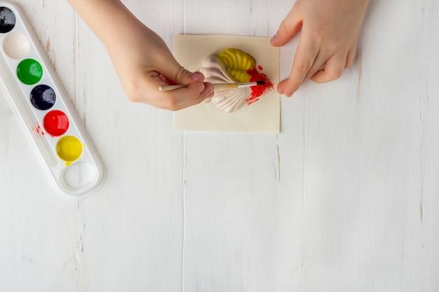 Instrukcja krok po kroku: jak wykonać formowanie gipsu (rysunki). koncepcja kreatywności diy i dzieci. robienie płaskorzeźb na magnesach. krok 7 kolorowanie gotowej figury ryby farbami przez dziecko