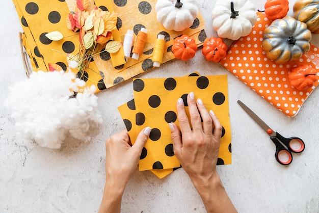 Instrukcja krok po kroku tworzenia tekstylnego rękodzieła z dyni na halloween. krok 1 - przygotowanie całego niezbędnego sprzętu. widok z góry na płasko