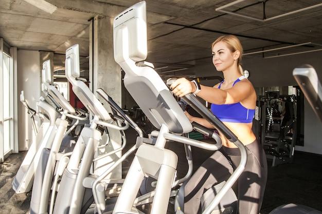 Instruktor blond kobieta w klubie fitness jeździ na orbitrack
