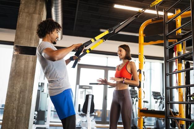 Instruktor fitness ćwiczący z osobami sprawnymi na siłowni.