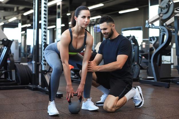 Instruktor fitness ćwiczący ze swoim klientem na siłowni.