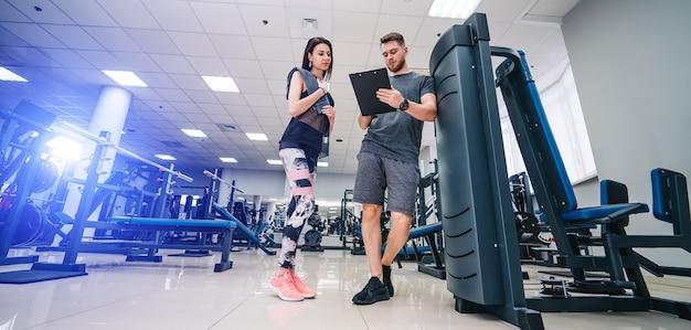 Instruktor fitness ćwiczy klienta na siłowni. harmonogram osobisty. selektywne skupienie. pojęcie zdrowia życia.