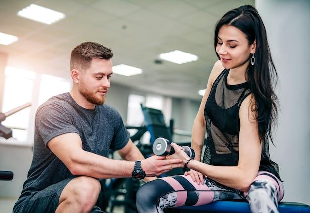 Instruktor fitness ćwiczy klienta na siłowni